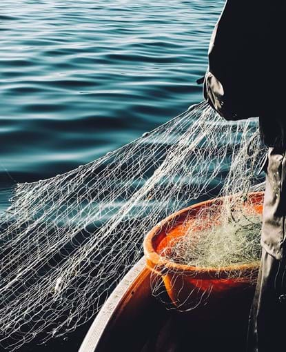A man pulling up a fishing net from the sea