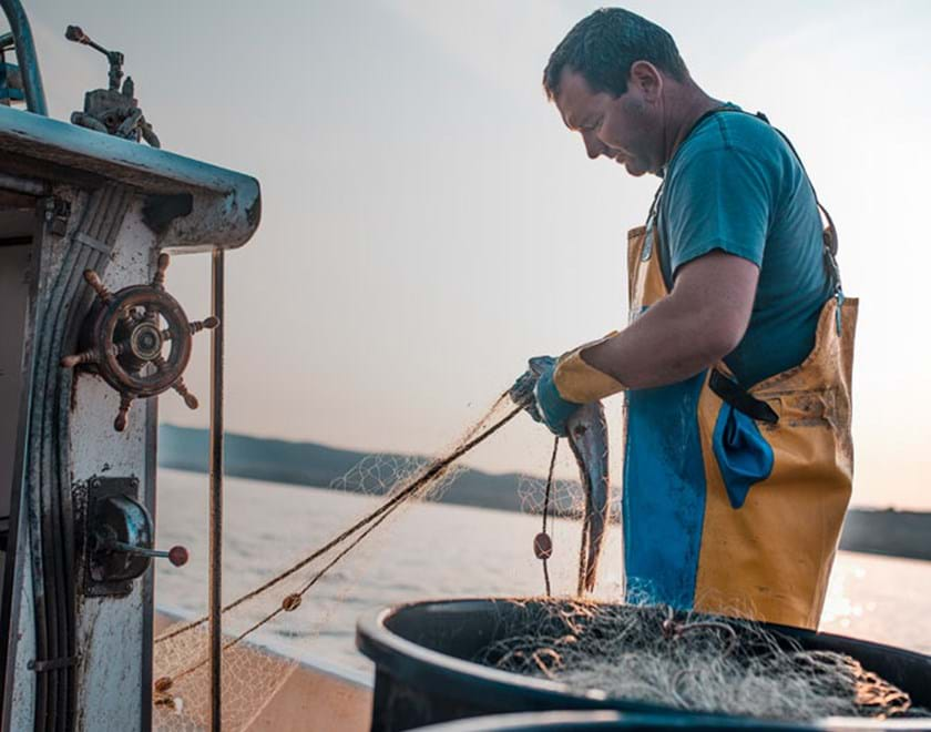 A man working with fishing nets at sea