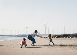 Family playing on beach with wind turbines in background