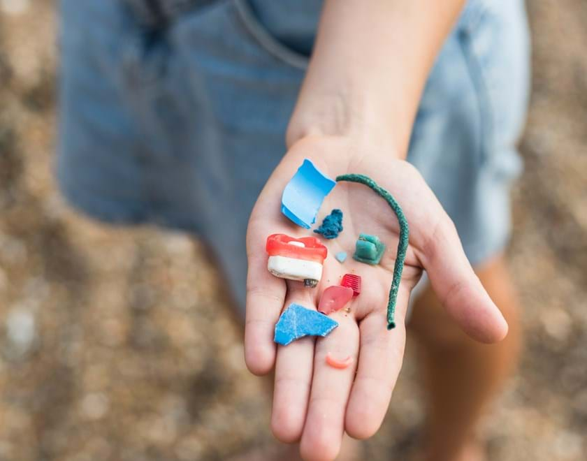 Child's hand holding pieces of plastic pollution