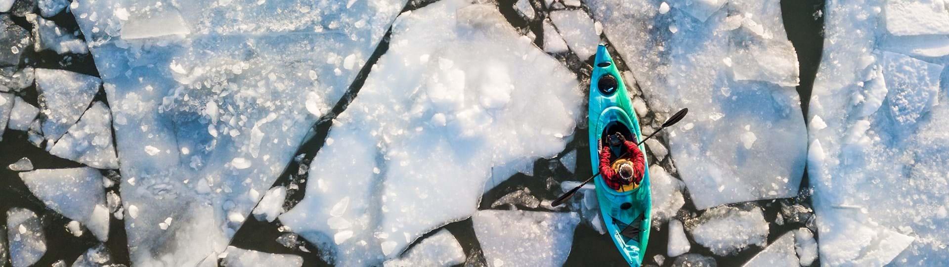 Man kayaking through ice
