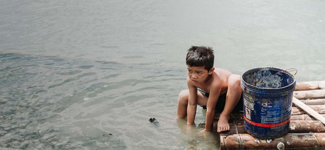 Boy washing in polluted water