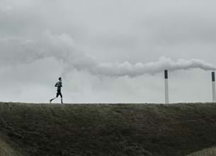 Man running in front of coal plant