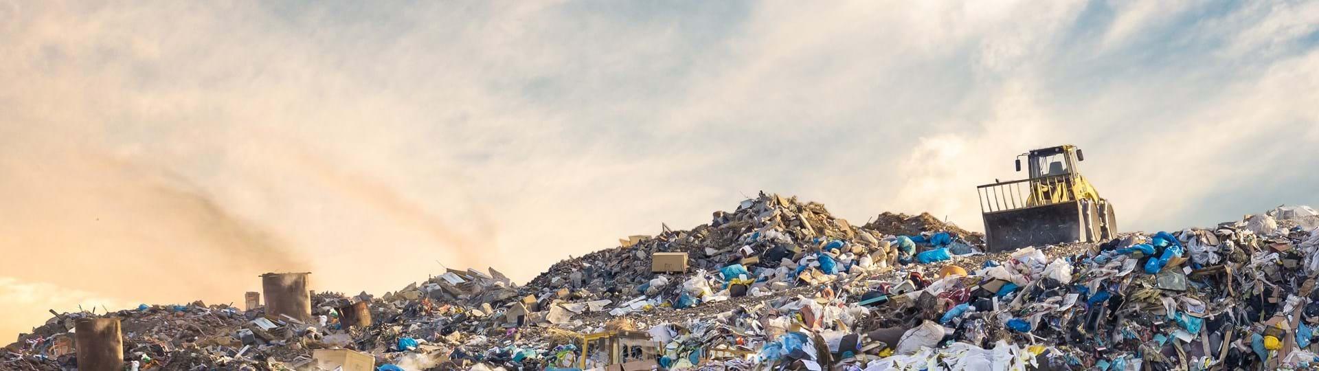 Bulldozer at a landfill site full of plastic