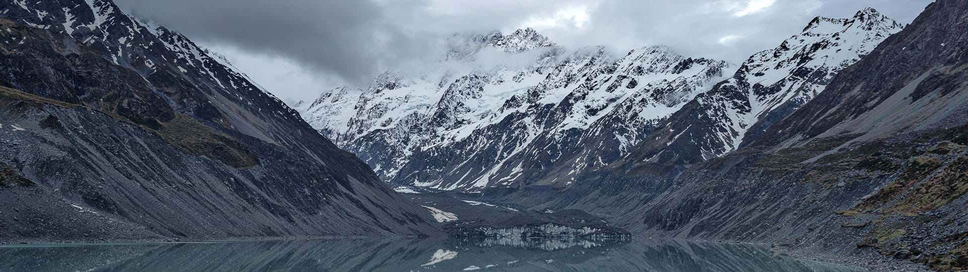 Man standing by body of water with mountains in the background